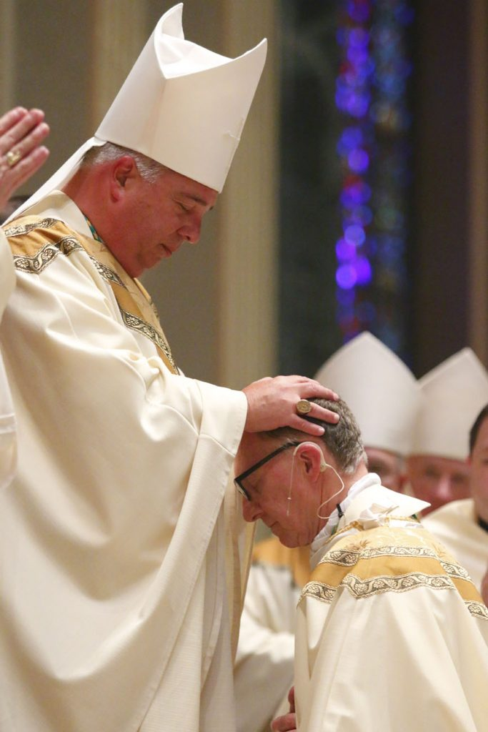Co-consecrator Bishop Nelson Perez, a former Philadelphia priest and now auxiliary bishop of the Diocese of Rockville Center, lays hands on his friend, Bishop Deliman. (Sarah Webb)