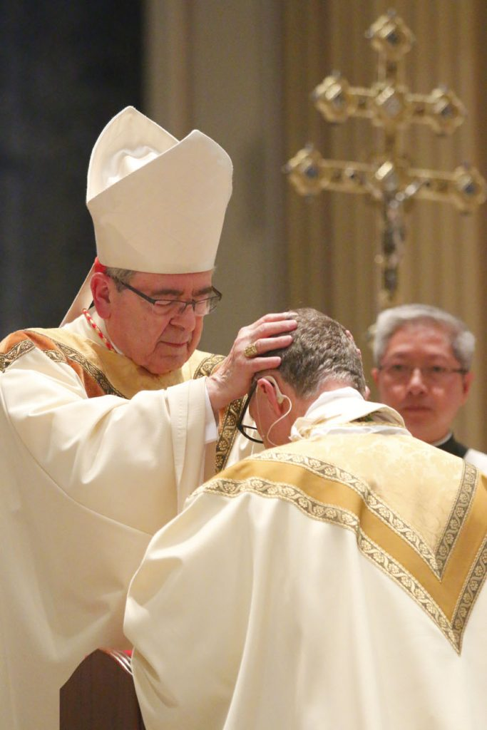 Cardinal Justin Rigali, retired archbishop of Philadelphia, lays hands on Bishop Deliman. (Sarah Webb)