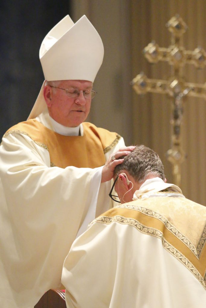 Archbishop Joseph Kurtz, head of the Archdiocese of Louisville and president of the United States Conference of Catholic Bishops, lays hands on the head of his friend Bishop Deliman. The two also studied at St. Charles Seminary together. (Sarah Webb)