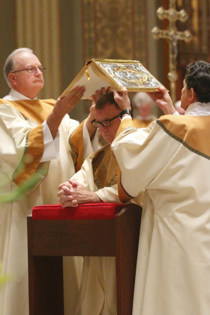 Deacons suspend the Book of Gospels over Bishop Deliman's head as Archbishop Chaput prays aloud. (Sarah Webb)