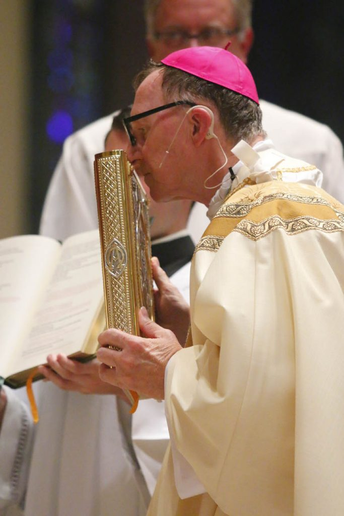 Bishop Deliman kisses the Book of Gospels. (Sarah Webb)