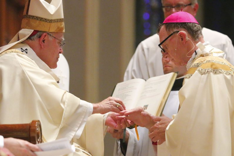 Bishop Deliman receives his episcopal ring, one of the three insignia of a Catholic bishop along with the mitre and crozier (a shepherd's staff) during the rite. (Sarah Webb)