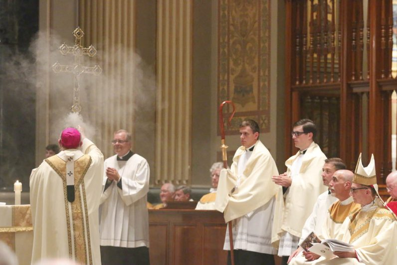 Archbishop Chaput incenses the processional cross in the cathedral's sanctuary. (Sarah Webb)