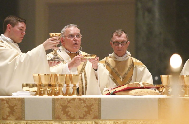 Archbishop Chaput celebrates the Liturgy of the Eucharist as Bishop Deliman concelebrates (right) and Transitional Deacon Matthew Brody assists at the altar. (Sarah Webb)