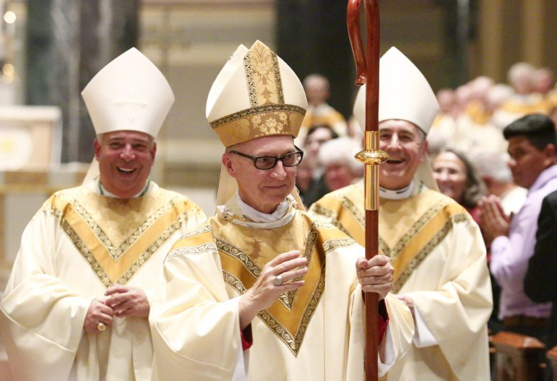 Bishop Edward M. Deliman greets worshipers at his Mass of ordination Thursday, Aug. 18 in the Cathedral Basilica of SS. Peter and Paul, Philadelphia. Two of his co-consecrators, Auxiliary Bishop Nelson Perez of the Rockville Center Diocese (left) and Harrisburg Bishop Ronald Gainer, accompany Bishop Deliman. (Photo by Sarah Webb)