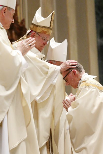 Archbishop Charles Chaput, principal consecrator and main celebrant of the ordination Mass, lays hands on Bishop Edward Deliman during the consecration rite. (Photo by Sarah Webb)