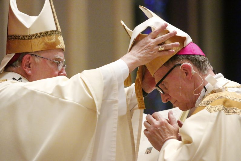 Archbishop Charles Chaput places the mitre -- one of the three insignia of a bishop along with the ring and crozier -- on the head of Auxiliary Bishop Edward Deliman Aug. 18 in the Cathedral Basilica of SS. Peter and Paul. (Sarah Webb)