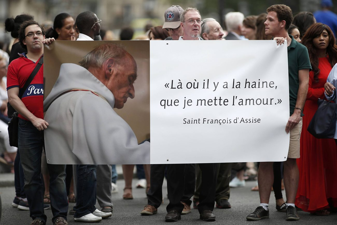 "People hold a banner with a picture of French priest Father Jacques Hamel, which reads, ""Where there is hatred, let me sow love,"" after a July 27 Mass at the Notre Dame Cathedral in Paris. Father Jacques Hamel was killed in a July 26 attack on a church at Saint-Etienne-du-Rouvray near Rouen by assailants linked to Islamic State groups. (CNS photo/Benoit Tessier, Reuters)"