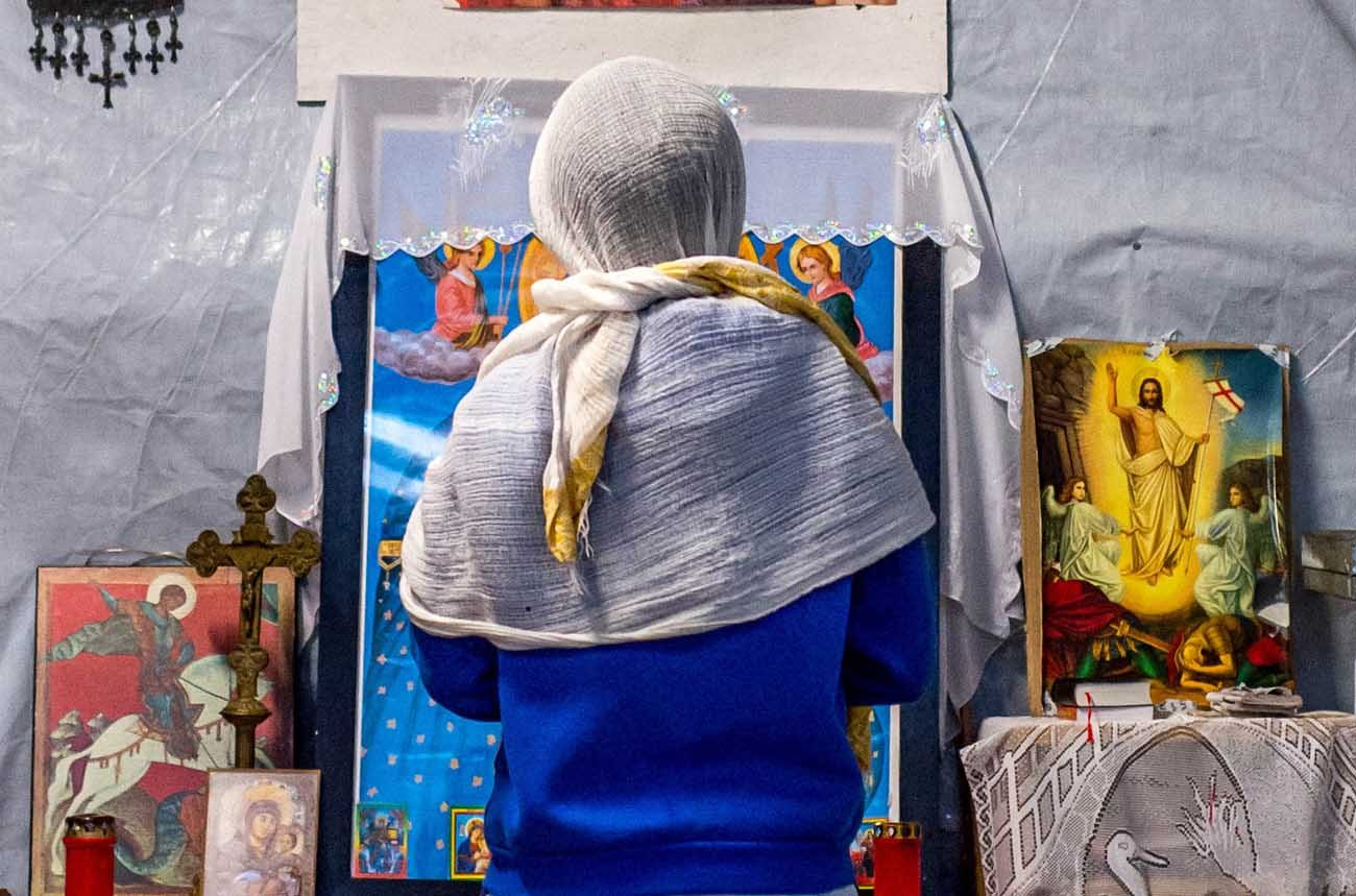 In 2015, a refugee prays Christmas day at a camp in Calais, France. Iraqi Christians appear divided about whether they will be able to return home after Islamic State militants are flushed out of the battle-scarred Ninevah Plains region. (CNS photo/Stephanie Lecocq, EPA)