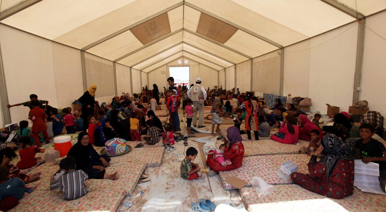 Displaced Iraqi people, who fled from Qayyarah because of Islamic State violence, gather July 16 at a refugee camp near Mosul, Iraq. (CNS photo/Azad Lashkari, Reuters)