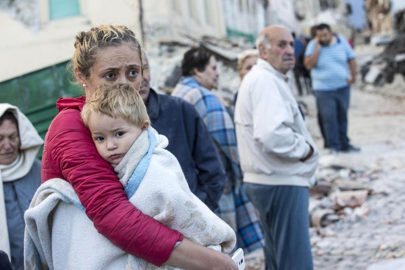 A mother embraces her son in Amatrice, Italy, following an earthquake Aug. 24. (CNS photo/Massimo Percossi, EPA)
