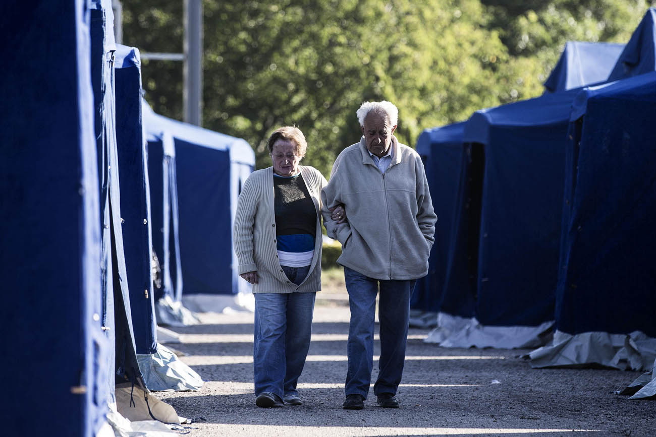 An elderly couple walks alongside tents Aug. 25 at a temporary camp for earthquake victims in Amatrice, Italy. The Aug. 24 quake left hundreds dead. (CNS photo/Angelo Carconi, EPA)
