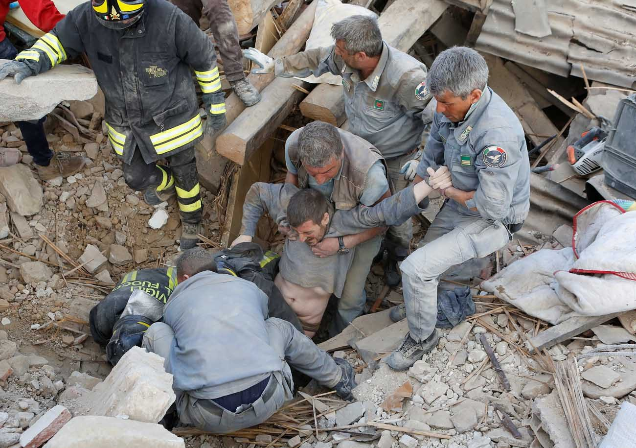 A man is rescued from the ruins following an earthquake in Amatrice, Italy, Aug. 24. (CNS photo/Remo Casilli, Reuters)