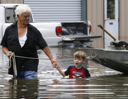 Richard Rossi and his 4-year-old great-grandson Justice wade through water Aug. 15 after their home flooded in St. Amant, La. (CNS photo/Jonathan Bachman, Reuters)