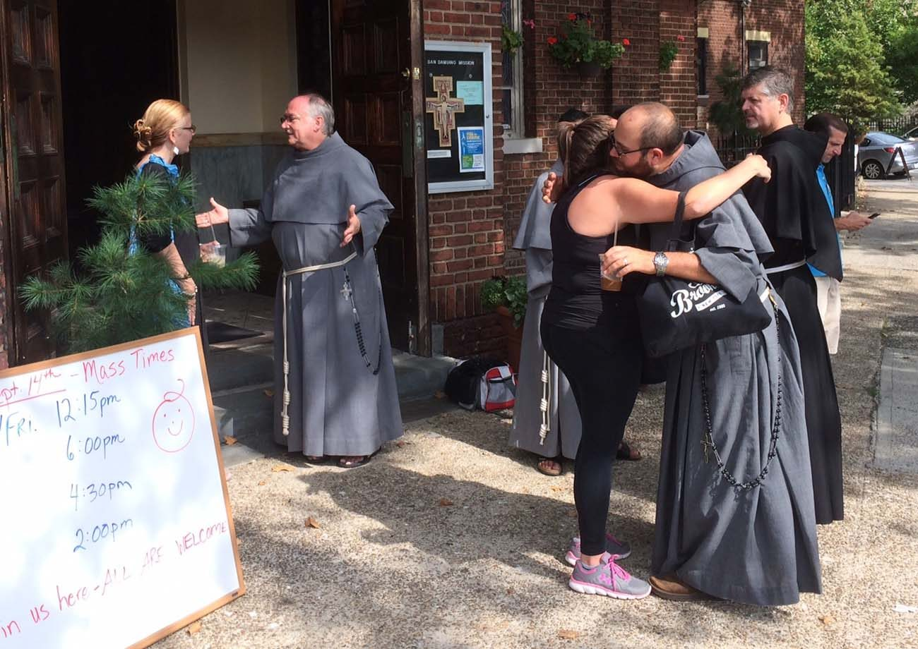 Conventual Franciscan friars greet the residents of the Greenpoint/Williamsburg section of Brooklyn, N.Y., Aug. 23, 2015, shortly after they opened their San Damiano Mission in the neighborhood, which had been the Holy Family (Slovak) Church. (CNS photo/Ed Wilkinson)