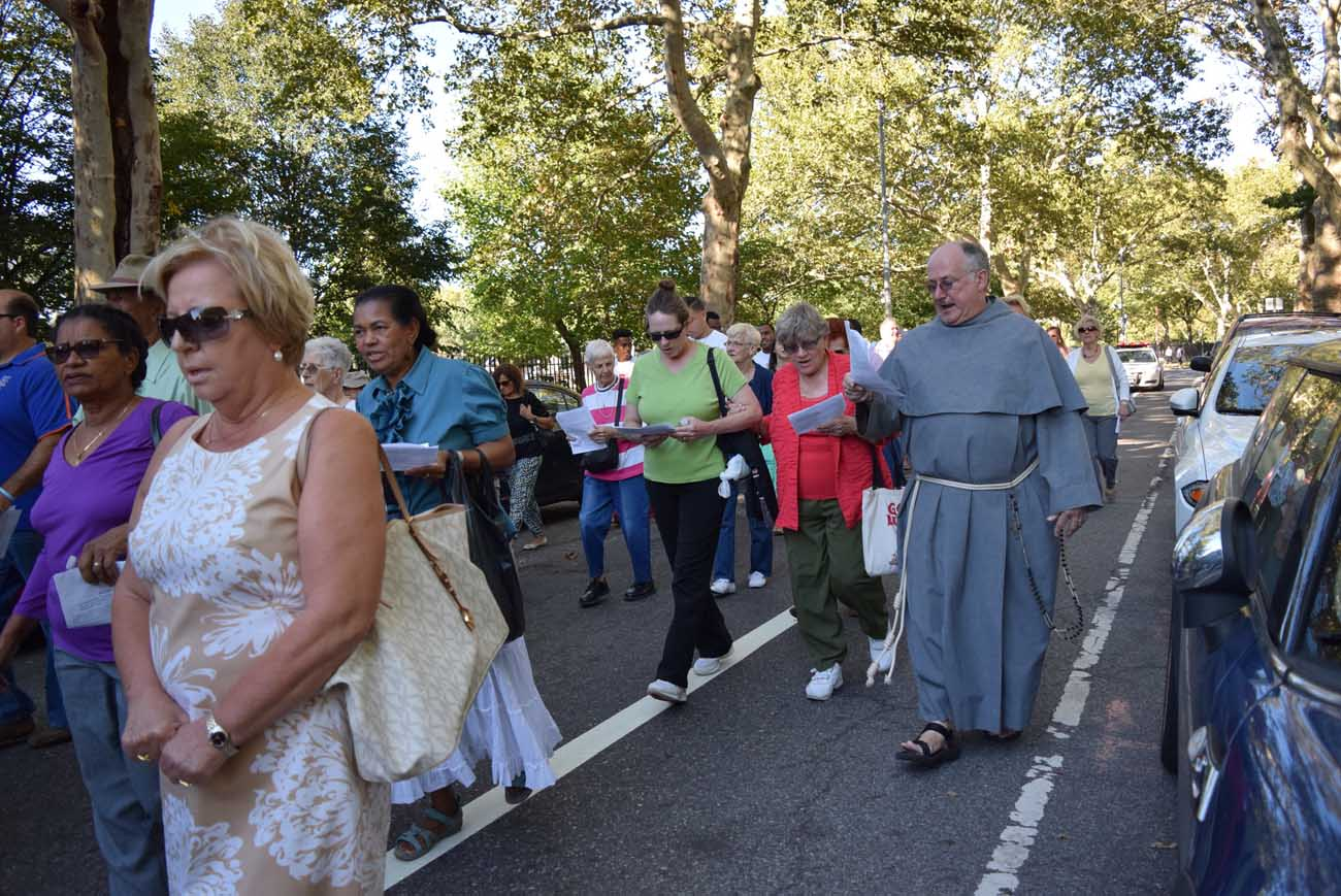 A Conventual Franciscan friar walks Sept. 20, 2015, with people who live near his San Damiano Mission in the Greenpoint/Williamsburg section of Brooklyn, N.Y. They were participating in an event sponsored by Catholic Charities Brooklyn and Queens in honor of the U.S. visit by Pope Francis. (CNS photo/Ed Wilkinson)
