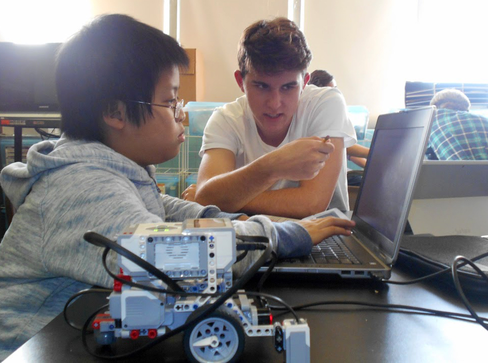 A teen volunteer helps a young Out of School Time Program participant at St. Helena/Incarnation School with his robotics project.