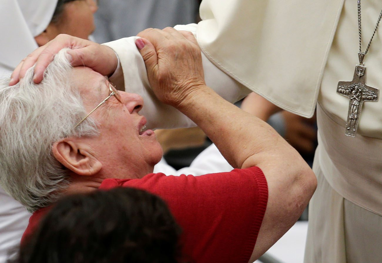 Pope Francis blesses a sick woman during his general audience in Paul VI hall at the Vatican Aug. 17. (CNS photo/Max Rossi, Reuters)