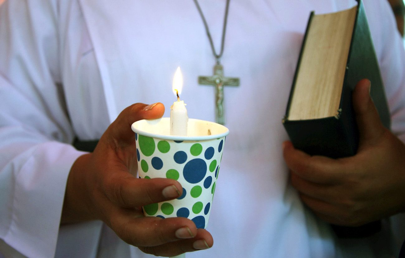 A Pakistani Christian in Karachi holds a candle during a vigil May 15, 2015. Christian social activists and jail authorities jointly inaugurated a chapel Aug. 5 at a Karachi jail with the help of a nongovernmental organization in Landhi.(CNS photo/Rehan Khan, EPA)