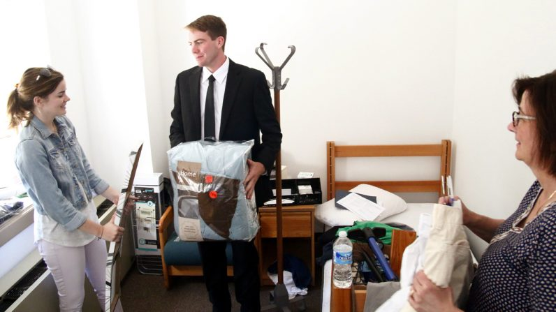 Robert Bollinger gets help from his sister Katherine and mom Karen as he moves into his room at St. Charles Seminary.