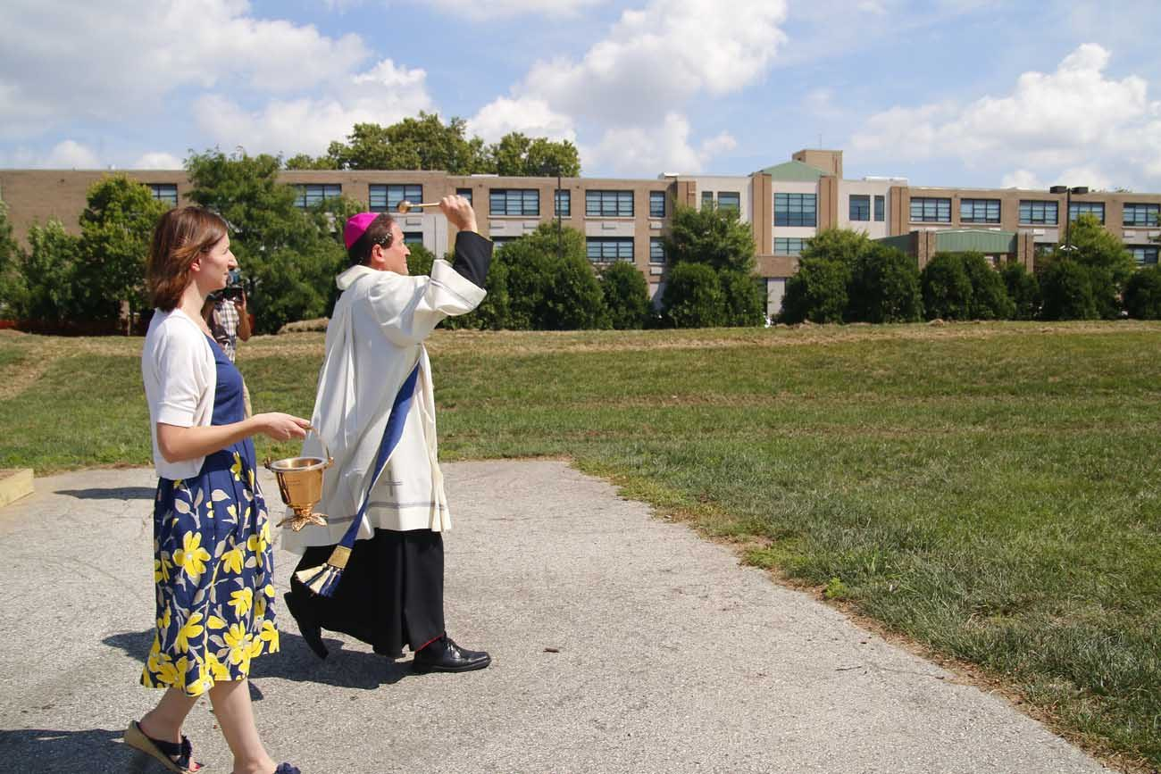 Auxiliary Bishop John McIntyre blesses the ground broken for St. John Neumann Place, the second phase of a senior housing project of the Archdiocese of Philadelphia expected to be completed by fall of 2017. Heather Huot of Catholic Health Care Services assists. (Photo by Sarah Webb)