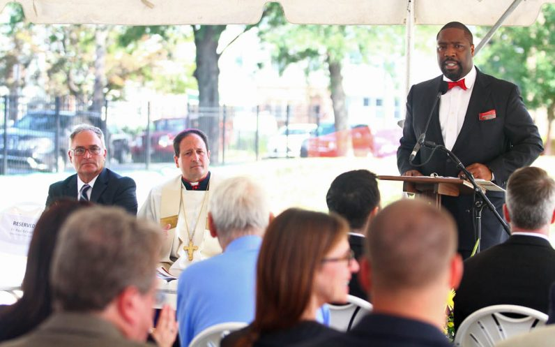 Philadelphia City Councilman Kenyatta Johnson, in whose South Philadelphia district St. John Neumann Place is located, speaks to the assembled guests as Bishop John McIntyre and James Amato, secretary for Catholic Human Services, look on.