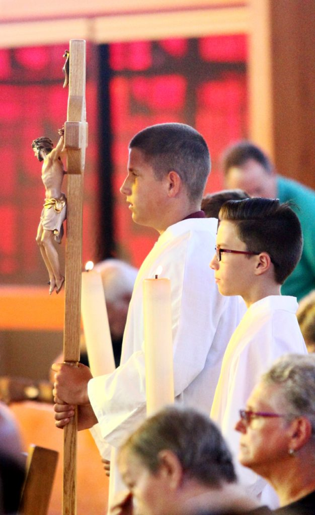 Altar servers Jared Susnoskie and Timothy Grindle prepare to process into church for Mass.