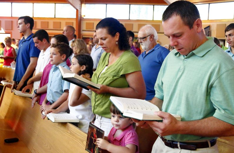 The Monastra family signs along to the opening hymn at the Sunday morning Mass.