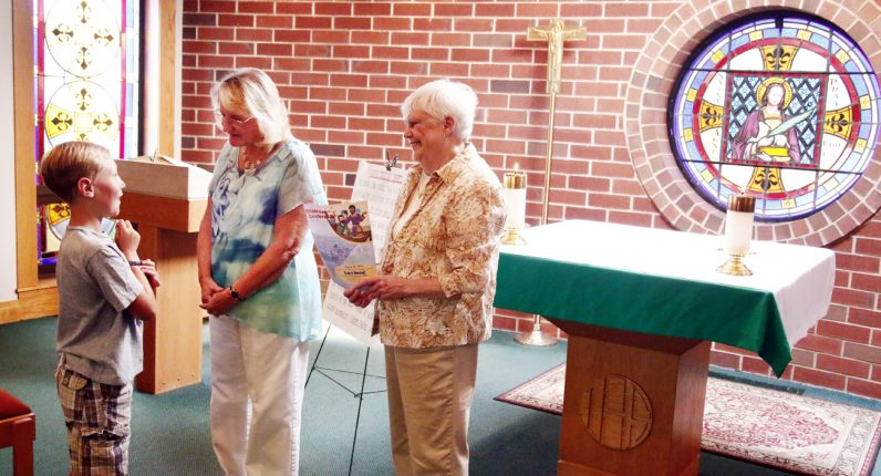 Tyler Frame talks with Clare Beard and Kay Moyer after the children's liturgy at the 10 a.m. Mass at St. Agnes in Sellersville. Eight different teams of parishioners volunteer to lead the Liturgy of the Word for children.