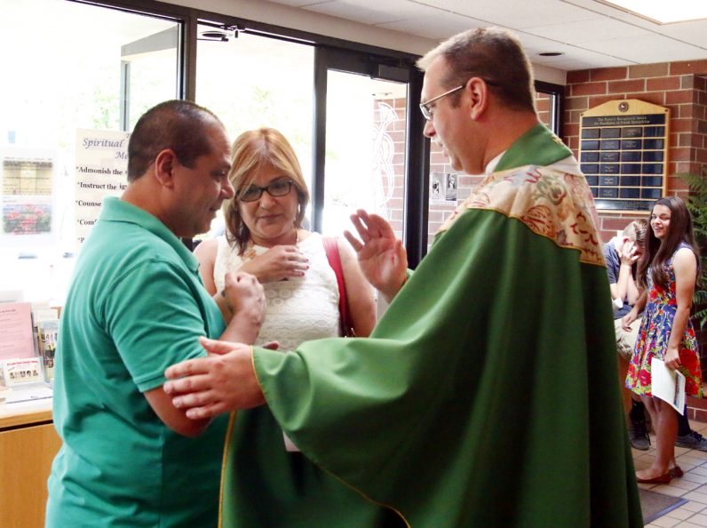 Father Jeffrey Stecz offers a blessing for Javier and Ivonne Gonzalez after Mass.