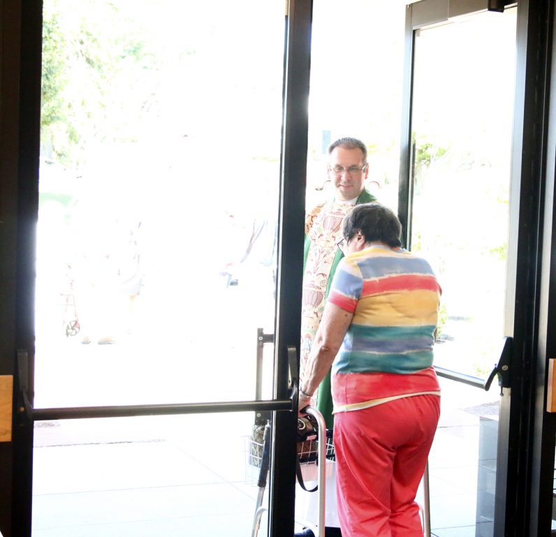 Father Jeffrey Stecz, pastor of St. Agnes, holds the door for a parishioner after Mass.