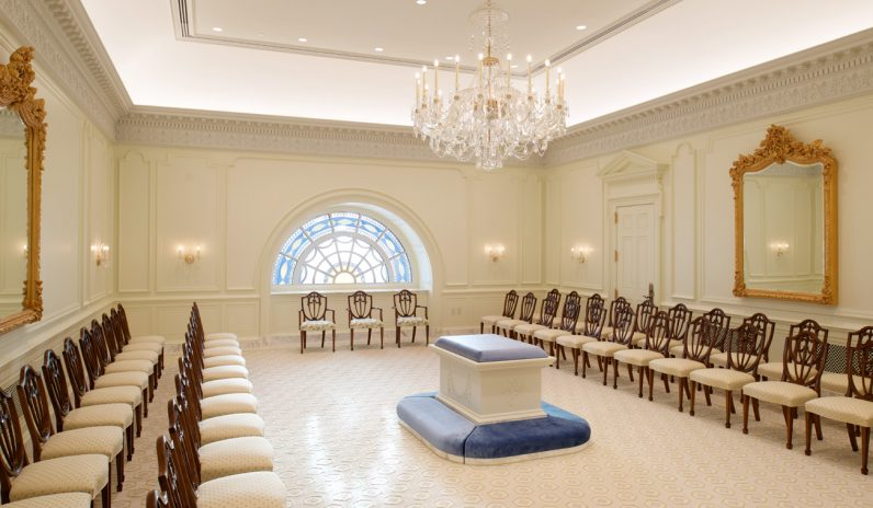 The Sealing Room on the fourth and top floor of the temple is the place where a Mormon couple, and perhaps their children, face each other around a central altar as they proclaim religious vows of love and union with Christ. Chairs for the ceremony's presiders and family members are also shown. (Photo by the Church of Jesus Christ of Latter-Day Saints)