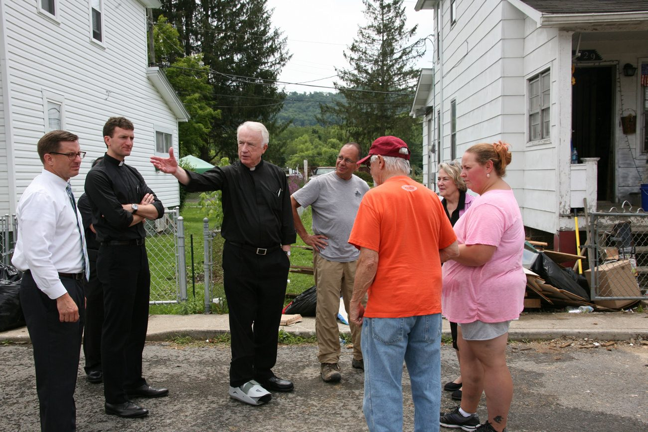 Bishop Michael J. Bransfield of Wheeling-Charleston, W.Va., tours a neighborhood in Rainelle, W.Va., July 25 that was ravaged by flood waters in June. (CNS photo/Tim Bishop, Catholic Spirit)