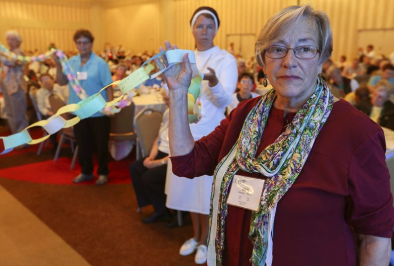 "Sister Meg Causey, a member of the Society of the Sacred Heart from Poughkeepsie, N.Y., right, stands with other sisters as they hold a ""chain of bondage."" Each link on the chain documents moments when an individual or her respective religious community was not welcomed to a person of color. A prayer and reconciliation service preceded the symbolic breaking of the chain. (CNS photo/Michael Alexander, Georgia Bulletin)"