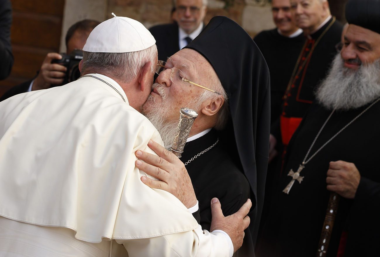 Pope Francis exchanges greetings with Ecumenical Patriarch Bartholomew of Constantinople as he arrives for an interfaith peace gathering at the Basilica of St. Francis in Assisi, Italy, Sept. 20. The peace gathering marks the 30th anniversary of the first peace encounter in Assisi in 1986. (CNS photo/Paul Haring)