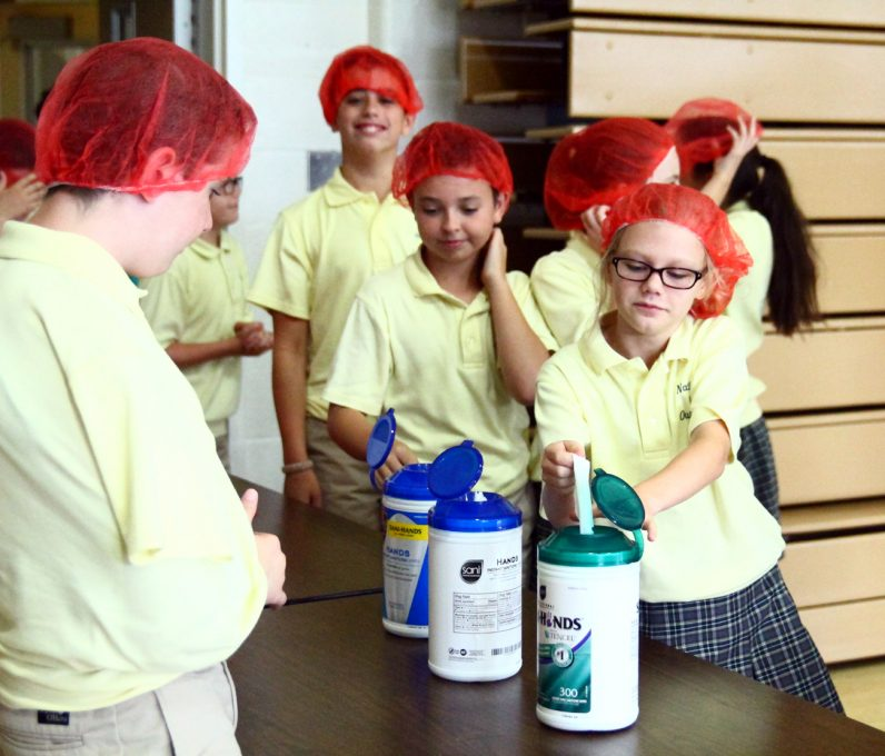 Students put on hairnets and sanitize their hands before preparing rice bags.