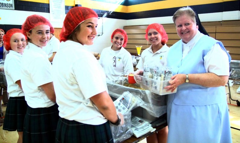 Sister Maureen McDermott, Superintendent for Secondary Schools, works with Archbishop Wood students to fill rice bags.