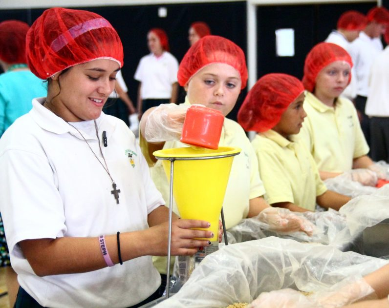 Students from Archbishop Wood High School work with students from Nativity of Our Lord School to make over 30,000 meals for those in need.