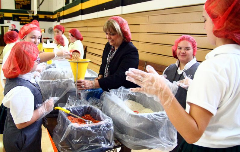 Debra Brillante, superintendent for elementary schools, works with students filling bags.