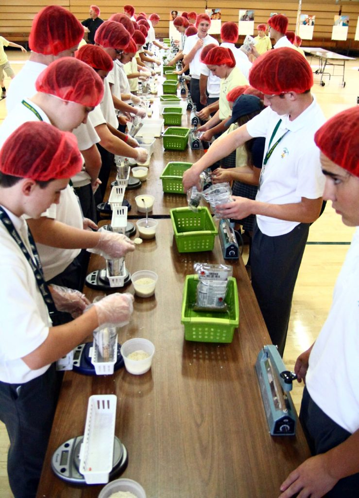 An assembly line weighs and seals the bags for food for CRS.