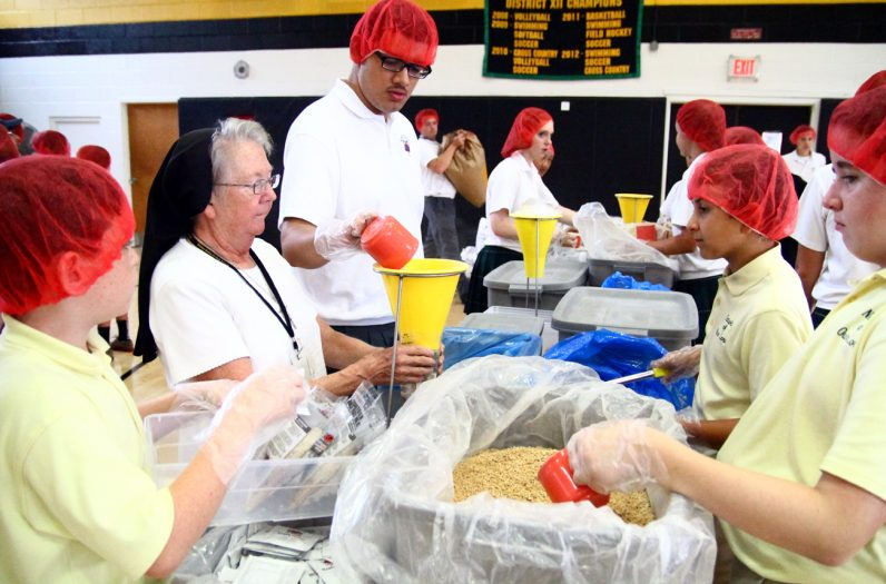 Sister Judith Moeller, I.H.M., principal of Our Lady of Confidence School, works with students filling bags with rice.