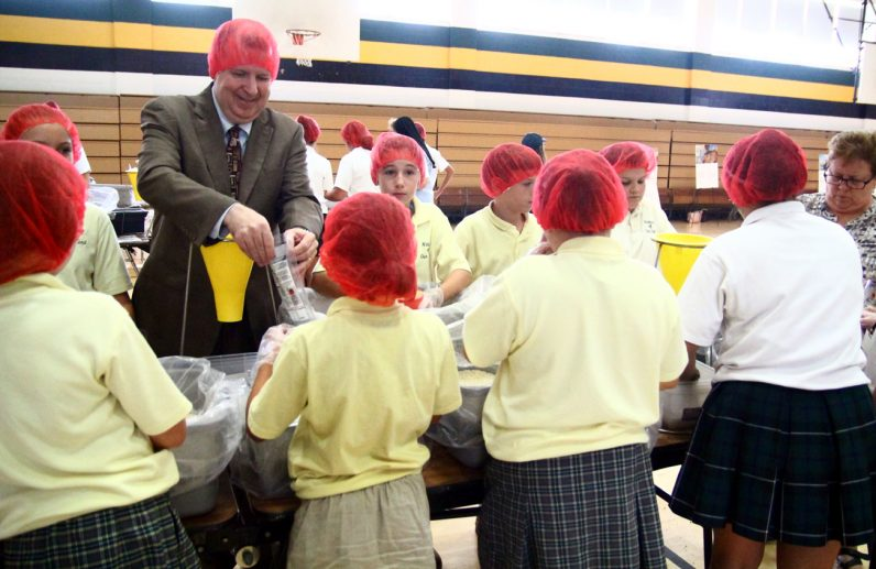 Francis Farrell, director of financial aid and scholarships program for the archdiocese, helps students make bags for CRS.