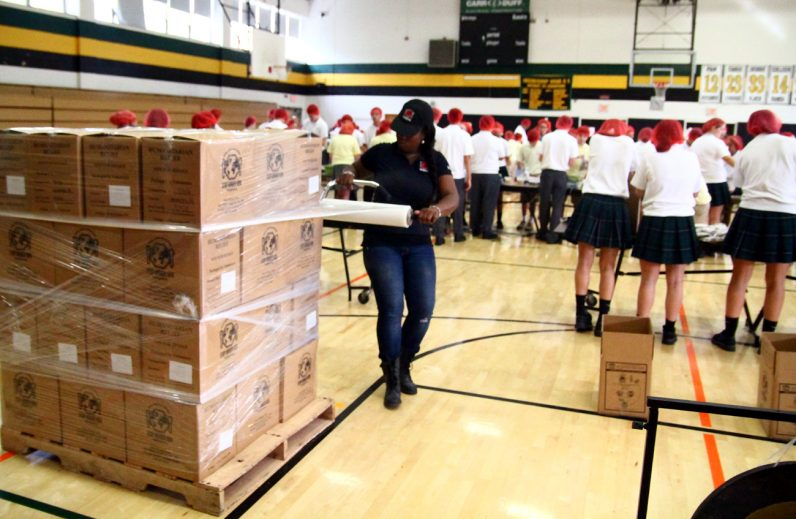 Latoya Gillyard, CRS/Stop Hunger Now logistics coordinator for Philadelphia, wraps a pallet of boxes with meals prepared by students from Archbishop Wood High School, Nativity of Our Lord School and Our Lady of Confidence School.