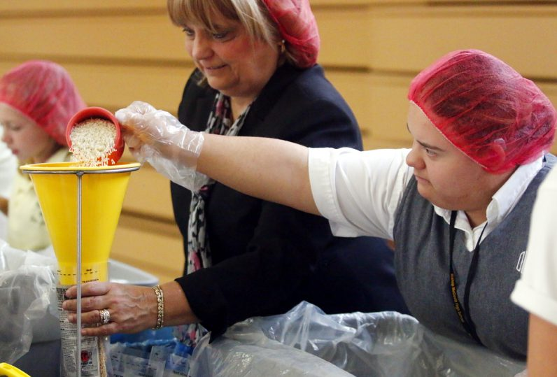 Jocelyn Maldonado (right) from Our Lady of Confidence fills rice into a bag that Debra Brillante, superintendent for elementary schools, holds open.