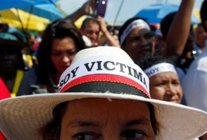 "A demonstrator with an ""I am a victim"" hat protests the government's peace accord with the Revolutionary Armed Forces of Colombia in Cartagena, Colombia, Sept. 26. The peace accord would allow rebels to enter parliament without serving any jail time. (CNS photo/John Vizcaino, Reuters)"