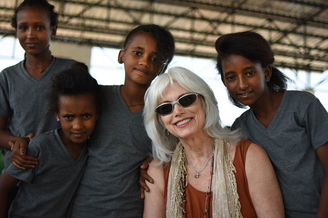 Emmylou Harris poses with young refugees at Adi-Harush refugee camp in northern Ethiopia. Harris, who has won more than a dozen Grammy awards during a 45-year career singing country music, is headlining a series of concerts this fall to benefit Jesuit Refugee Service. (CNS photo/Christian Fuchs, Jesuit Refugee Service/USA)