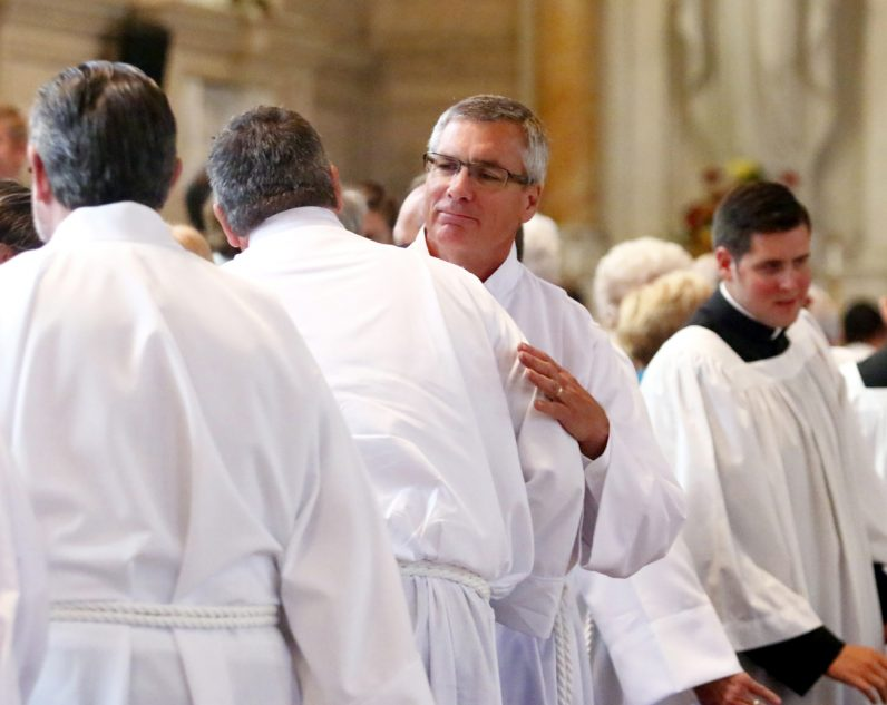 Gregg Hoyer offers a sign of peace to his fellow diaconate candidate.