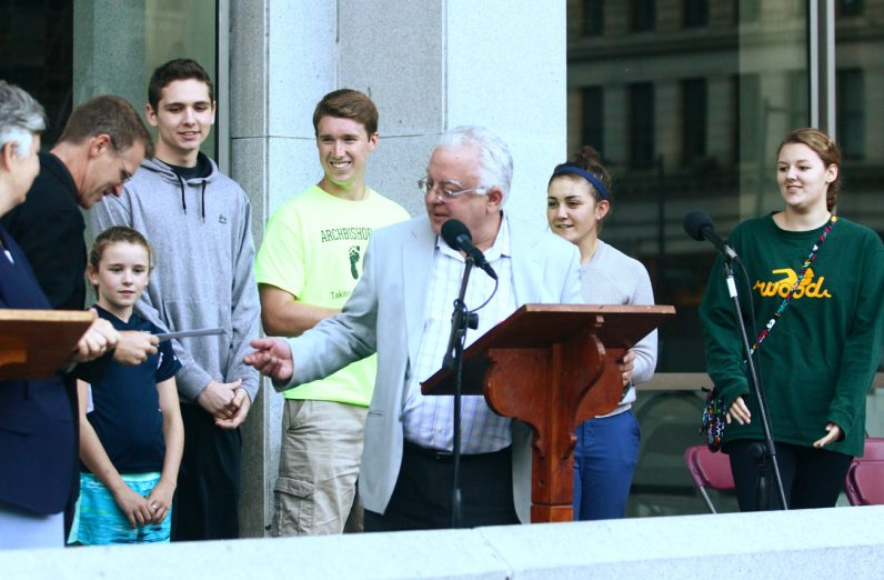 Steven Bozza, director of the archdiocesan Office for Life and Family, awards a group of Archbishop Wood High School students that they won the office's contest for best pro-life video.