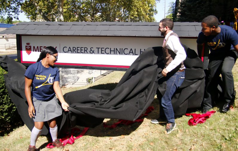 Ashlee Upchurch, Mercy CTE Student Council president, and George Matysik, class of 1999, unveil the new sign in front of the school on Hunting Park Avenue in Philadelphia.