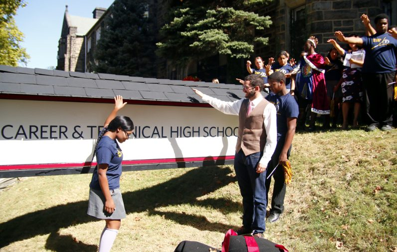 Students and those in attendance extend their arms over the new sign in prayer for the blessing.